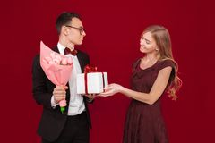 Elegancki mężczyzna w kostiumu daje pudełku z prezentem i bukietowi kwiaty piękna kobieta na czerwonym tle dzień kobiety s obrazy stock