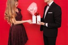 Elegancki mężczyzna w kostiumu daje pudełku z prezentem i bukietowi kwiaty piękna kobieta na czerwonym tle dzień kobiety s zdjęcia stock