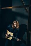 Elegancki mężczyzna w kostiumu i okularach przeciwsłonecznych bawić się gitarę na czerni Zdjęcia Stock