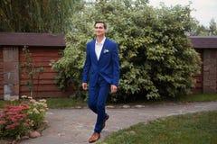 Elegancki mężczyzna w kostiumu uczepienia guzikach na jego kurtki narządzaniu wychodził obraz stock