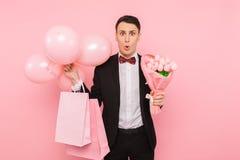 Elegancki mężczyzna w kostiumu z wiązką kwiaty torby i balony, na różowym tle pojęcie kobieta dzień obrazy stock