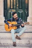 Elegancki mężczyzna z brodą w szkockiej kraty koszula, cajgach w ulicie na krokach blisko drzwi i Macho z pięknym uśmiechem siedz Zdjęcia Royalty Free