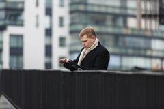 Elegancki mężczyzna z gadżetem na miastowym tle Zdjęcia Royalty Free