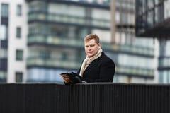 Elegancki mężczyzna z gadżetem na miastowym tle Obrazy Royalty Free