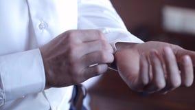 Elegancki mężczyzna zapina mankieciki jego koszula zbiory
