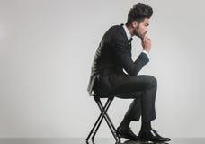Elegancki młodego człowieka obsiadanie na główkowaniu i stolec obrazy royalty free