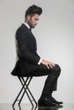 Elegancki młodego człowieka obsiadanie na stolec patrzeje puszek Zdjęcie Royalty Free