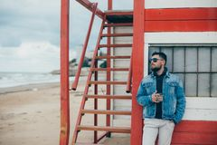 Elegancki młody człowiek stoi blisko oceanu z filiżanką herbata z brodą obrazy royalty free
