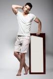 Elegancki młody człowiek w Białej bawełnie Odziewa z Deskową pozycją Fotografia Stock