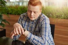 Elegancki młody facet jest ubranym sprawdzać koszulowego z czerwonym włosy i piegami patrzejący jego zegarka czekanie dla spotkan Zdjęcie Royalty Free