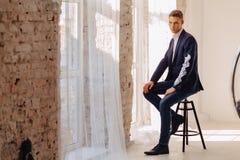 Elegancki młody facet w kostiumu z monumentalną twarzą w świecącym wnętrzu, moda, biznesu akcent zdjęcie stock