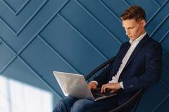 Elegancki młody facet z laptopem, młody biznesmen, freelancer praca, aqua tło fotografia royalty free