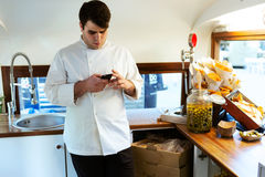 Elegancki młody szef kuchni używa jego telefon komórkowego w karmowej ciężarówce Fotografia Stock