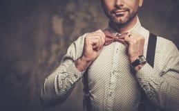 Elegancki mężczyzna jest ubranym suspenders i pozuje na ciemnym tle z łęku krawatem Zdjęcia Royalty Free