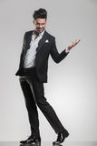 Elegancki mężczyzna odprowadzenie podczas gdy trzymający jeden rękę w powietrzu Obrazy Stock