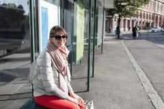 Elegancki modniś dziewczyny obsiadanie na autobusowej przerwie w wiosna słonecznym dniu modnej kobiety turystyczny czekanie dla m obraz stock