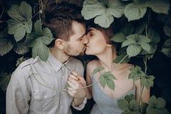Elegancki modniś pary całowanie w zieleni opuszcza, mienie ręki M zdjęcie royalty free