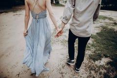 Elegancki modniś pary odprowadzenie, mienie ręki mężczyzna i kobiety emb obrazy royalty free