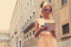 Elegancki modniś studiuje mapę podczas gdy stojący w miastowym położeniu w lecie, Obraz Stock