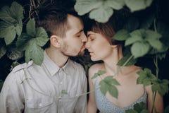 Elegancki modnisia państwa młodzi całowanie w zielonych liściach, mienie zdjęcie stock