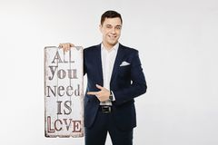 Elegancki, modny i przystojny młody brunetka mężczyzna w zmroku w białej koszula i, - błękitny kostium, uśmiecha się znaka w, trz fotografia royalty free
