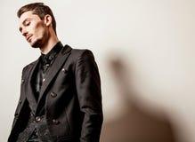 Elegancki młody przystojny mężczyzna w czarnym kostiumu Pracowniany moda portret Obrazy Stock