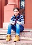 Elegancki nastoletni chłopak z hełmofonami, siedzi na schodkach zdjęcia stock