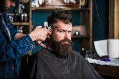 Elegancki ostrzyżenia pojęcie Ręki fryzjer męski z cążki zakończeniem up Modnisia brodaty klient na surowej twarzy dostaje fryzur obraz stock