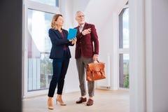 Elegancki piękny pośrednik w handlu nieruchomościami jest ubranym błękitnego kostium opowiada jej klient obraz stock