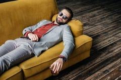 elegancki pijący mężczyzna trzyma szkło whisky i lying on the beach w okularach przeciwsłonecznych obrazy stock