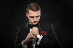 Elegancki potomstwo mody mężczyzna patrzeje jego zegarek Zdjęcia Stock