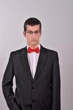 Elegancki potomstwo mody mężczyzna w smokingu trzyma jego prawą rękę wewnątrz Zdjęcie Royalty Free