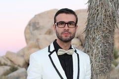 Elegancki potomstwo mody mężczyzna z szkłami w smokingu strzelał przy zmierzchem w Joshua drzewa parku narodowym, Kalifornia, usa Zdjęcie Stock