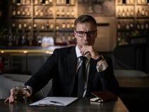 Elegancki, poważny i skoncentrowany biznesmen, trzyma szkło whisky i patrzeje kamerę zdjęcia stock