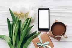 Elegancki prezent i opróżnia telefon, tulipany i kawa na białym drewnie Obraz Stock