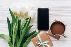 Elegancki prezent, telefon, tulipany i kawa na białym drewnianym Rus Zdjęcie Stock