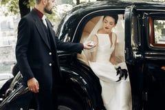 Elegancki przystojny elegancki fornal pomaga delikatnie wspaniałej panny młodej, ho Obraz Stock