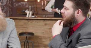 Elegancki przystojny młody człowiek z ładną brodą opowiada z jego partnerem biznesowym zbiory