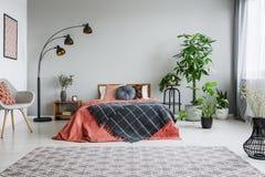 Elegancki siwieje krzesła, czarnej metal lampy, drewnianego wezgłowie stołu i wygodnego królewiątko rozmiaru łóżka, istna fotogra fotografia stock