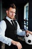 Elegancki sportowy mężczyzna w garniturze i piłki nożnej piłce Przeciw tłu loft ściana Obrazy Stock