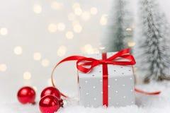 Elegancki srebny prezenta pudełko wiążący z czerwoną jedwabniczą tasiemkową łęk zimy sceną w lesie z jedlinowych drzew baubles w  fotografia stock