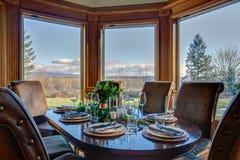 Elegancki stół ustawia dla obiadowego i pięknego nadokiennego widoku obraz stock