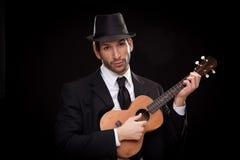 Elegancki szczęśliwy mężczyzna piosenkarza muzyk bawić się ukulele gitarę odizolowywającą na czerni Fotografia Stock