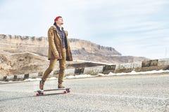 Elegancki szczęśliwy Młody facet w spodń joggers tocznym puszku i nakrętce halna droga na longboard, cieszy się życie zdjęcie stock