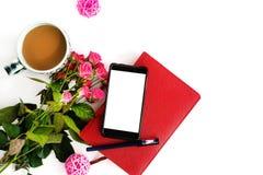 Elegancki telefon z pustym ekranem i różami kawa dalej i notatnik zdjęcie royalty free