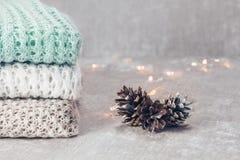 Elegancki trykotowy pastel barwił pulowery składających w stercie z sosnowymi rożkami na velvety tkaniny tle Zamyka w górę, kopia obrazy stock