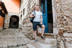 Elegancki turystyczny mężczyzna ubierał w białej koszula i skrótach z plecakiem nad jego ramieniem Stać na krokach Europejski mia Zdjęcia Stock
