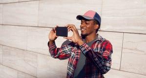 Elegancki uśmiechnięty afrykański mężczyzna bierze selfie obrazek telefonem w baseball nakrętce, szkockiej kraty koszula na miast zdjęcia stock
