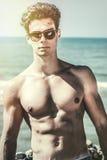Elegancki uwodziciela mężczyzna przy morzem Moda okulary przeciwsłoneczni i włosiany styl obraz stock