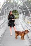 Elegancki w krótkiej sukni trzyma kołnierza purebred psa na moście obraz royalty free